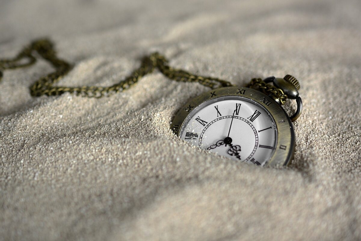 watch buried in brown sand showing time - stress releasing mantras